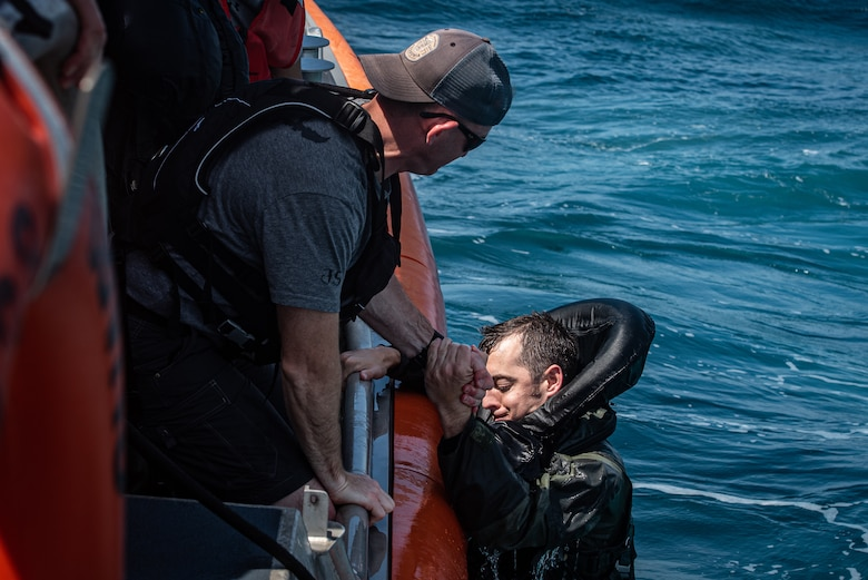 U.S. Air Force Tech. Sgt. David Jones, 20th Operations Support Squadron survival, evasion, resistance and escape non-commissioned officer in charge (left) helps U.S. Air Force Capt. Scott Brandon out of the water off the coast of Tybee Island Coast Guard Station, Georgia, June 21. 2019.