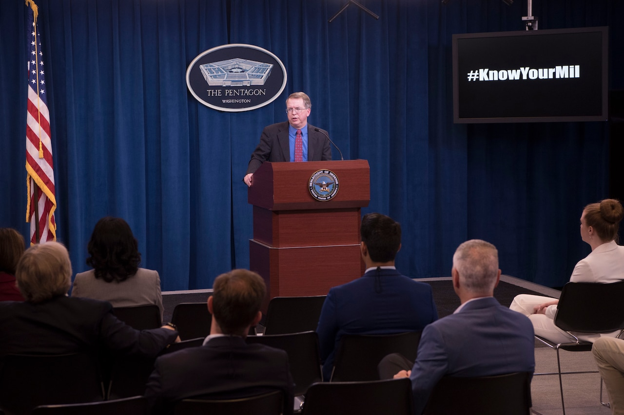 A man speaks from behind a podium.