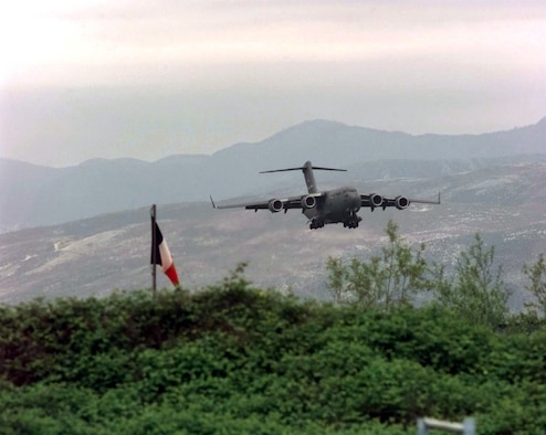 A U.S. Air Force C-17 Globemaster III from Joint Base Charleston makes its final approach to Rinas Airport in Albania during Operation Shining Hope, April 23, 1999. Medical Airmen provided humanitarian support for ethnic Albanian refugees fleeing Kosovo (U.S. Air Force illustration by Tech. Sgt. Cesar Rodriguez)