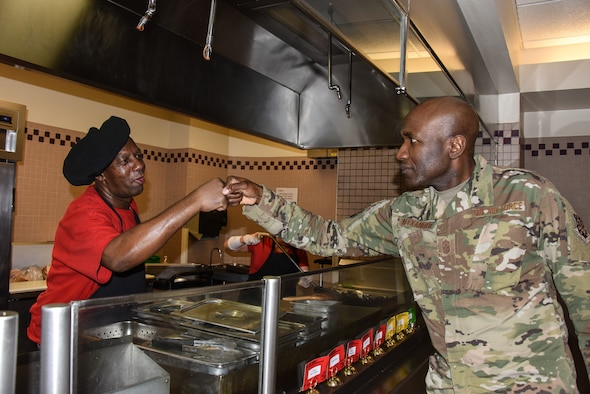 Gosnel James, grill cook at the Dish dining facility, prepares a hamburger for a customer during lunch time at Schriever Air Force Base, Colorado, June 14, 2019. Caribbean-American Heritage month is celebrated during June, recognizing the significance of Caribbean people and their heritage in the culture and history of the United States. (U.S. Air Force photo by 2nd Lt. Idalí Beltré Acevedo)