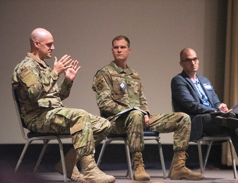 Maj. Zachary McCarty (left), Maj. Matthew Getts and Dr. Michael Tanner discuss a variety of topics during the Implementing Acquisition Transformation panel.(U.S. Air Force photo by R.J. Oriez)