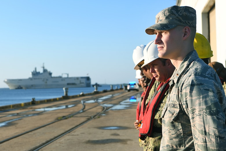 U.S. Air Force 2nd Lt. Jonathon Mogan, assigned to the 437th Aerial Port Squadron, watches the Marine Nationale (French Navy) Landing Helicopter Dock Tonnerre move toward the Charleston Terminal Port as part of a deployment stopover June 21, 2019, in Charleston, S.C. U.S. Navy Cmdr. Patrick Sutton, Naval Support Activity Charleston executive officer and 628th Mission Support Group deputy commander, spoke with leaders of LHD Tonnerre to ensure the crew received support during their stay in Charleston. Engagements such as this provide opportunities to strengthen partnerships between allies.