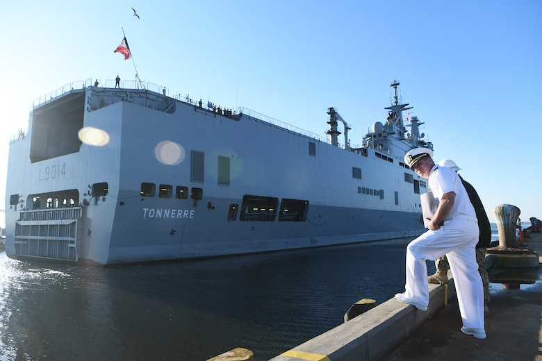 U.S. Navy Cmdr. Patrick Sutton, Naval Support Activity Charleston executive officer and 628th Mission Support Group deputy commander, waits for the Marine Nationale (French Navy) Landing Helicopter Dock Tonnerre to dock at the Columbus Terminal Port as part of a deployment stopover June 21, 2019, in Charleston, S.C. Sutton and Sailors of the 628th Logistics Readiness Squadron waterfront port operations spoke with leaders of LHD Tonnerre to ensure the crew received support during their stay in Charleston. Engagements such as this provide opportunities to strengthen partnerships between allies.