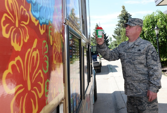 U.S. Air Force Master Sgt. Vicent Lopez, 55th Aircraft Maintenance Squadron, receives a tropical flavored shaved ice June 20, 2019, during a morale event at the Warhawk Community Center on Offutt Air Force Base, Nebraska. Shaved ice was served to team Offutt members at the Warhawk Community Center, 55th Wing Base Operations building and the Martin Bomber building. (U.S. Air Force photo by Charles J. Haymond)