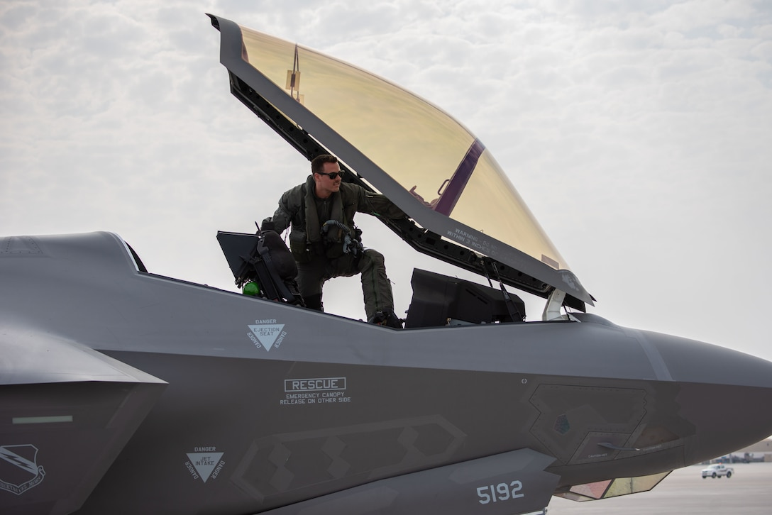 A photo of an F-35A pilot entering the cockpit.