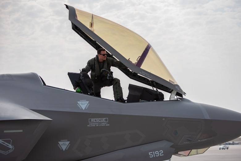 A photo of an F-35A pilot entering the cockpit.