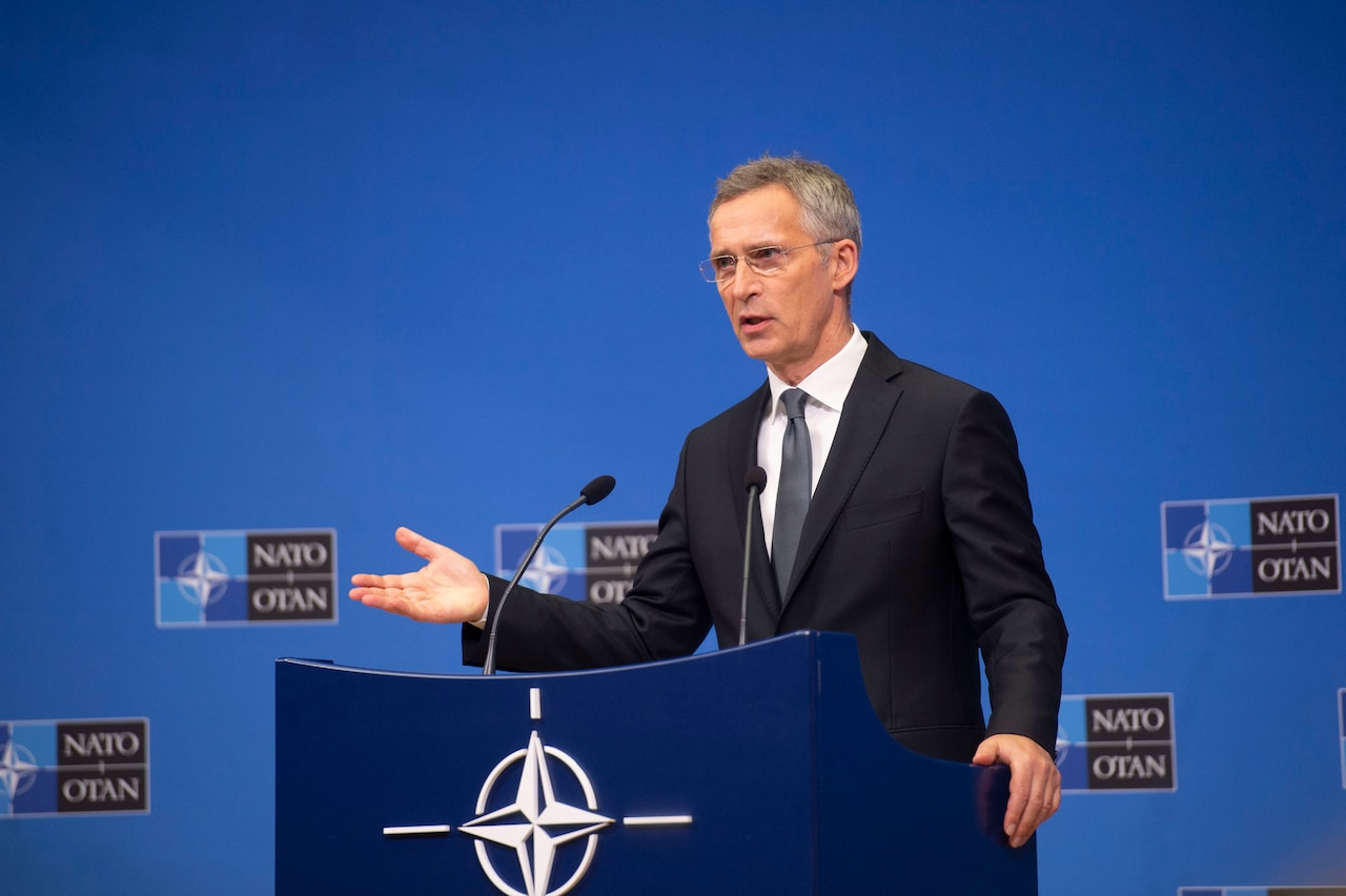 A man in large room speaks at a dias.