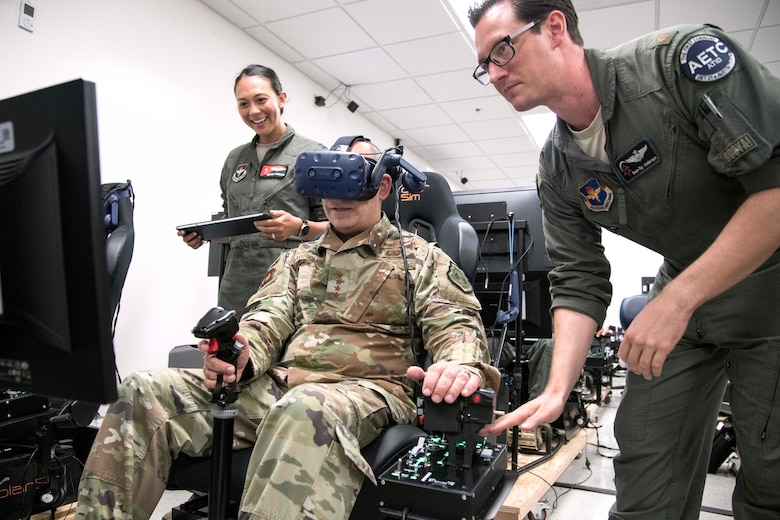 Gen. Jeffrey L. Harrigian (center), United States Air Forces Europe and United States Air Forces Africa commander, uses a virtual reality flight simulator during a visit to Detachment 24 at Joint Base San Antonio-Randolph, Texas, June 24, 2019.  PTN is an Air Education and Training Command program to explore and prototype a pilot training environment that integrates various technologies to produce pilots in a learning-focused manner. (U.S. Air Force photo by Sean M. Worrell)