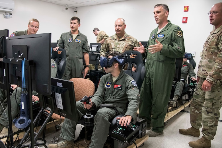 Lt. Col. Brandon Zuercher (right), instructor pilot, briefs Gen. Jeffrey L. Harrigian, United States Air Forces Europe and United States Air Forces Africa commander, on the virtual reality simulator capabilities during a visit to Detachment 24 at Joint Base San Antonio-Randolph, Texas, June 24, 2019.  Det. 24 will absorb the third and future iterations of Pilot Training Next, Air Education and Training Command's initiative to redesign the pilot training environment and integrate various technologies to produce pilots in a learning-focused manner.  (U.S. Air Force photo by Sean M. Worrell)