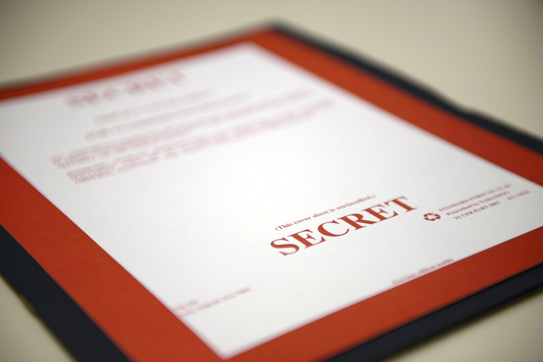 "A blue folder bears a red and white cover sheet marked ""SECRET."""