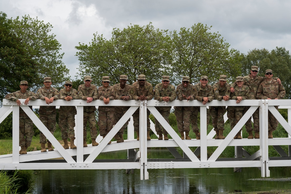 Airmen from the 23d Civil Engineer Squadron pose for a photo, June 5, 2019, in Sainte-Mère-Église, France. The engineers provided structural support for the Commemoration of D-Day 75 by repairing and building bridges that were used to access hard-to-reach areas of a parachute drop zone. As part of the commemoration, parachutists from across the Department of Defense performed the same jumps their predecessors did on D-Day. (U.S. Air Force photo by Airman 1st Class Hayden Legg)