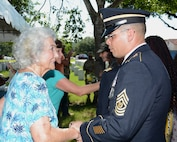 Command Sgt. Maj. Gilberto Colon, 187th Medical Battalion, greets Rita Van Autreve during a ceremony honoring retired Sgt. Maj. of the Army Leon Van Autreve at a June 21 ceremony at the Fort Sam Houston National Cemetery.