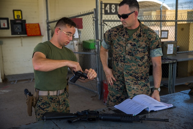 U.S. Marine Corps Lance Cpl. Tyler Huckleberry and U.S. Navy sailor HM2 David Manley, with Headquarters & Headquarters Squadron Marine Corps Air Station (MCAS) Yuma, conduct weapons training in order to qualify for the Enlisted Fleet Marine Force Warfare Specialist device on MCAS Yuma, June 11, 2019. In order to be awarded the device, a sailor must complete the Fleet Marine Force Qualification Training in order to familiarize themselves with the Marine Corps. (U.S. Marine Corps photo by Lance Cpl. John Hall)