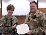 Defense Logistics Agency Indo-Pacific Commander Navy Capt. Kristin Acquavella presents an award to DLA Indo-Pacific Military Deputy Commander Army Col. Brent Coryell at Camp Humphreys, Korea.