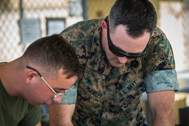 U.S. Marine Corps Lance Cpl. Tyler Huckleberry and U.S. Navy sailor HM2 David Manley, with Headquarters & Headquarters Squadron Marine Corps Air Station (MCAS) Yuma, conduct weapons training in order to qualify for the Enlisted Fleet Marine Force Warfare Specialist device on MCAS Yuma, June 11, 2019. In order to be awarded the device a sailor must complete the Fleet Marine Force Qualification Training in order to familiarize themselves with the Marine Corps. (U.S. Marine Corps photo by Sgt. Isaac D. Martinez)