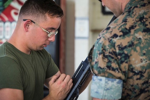 U.S. Marine Corps Lance Cpl. Tyler Huckleberry and U.S. Navy sailor HM2 Davidl Manley, with Headquarters & Headquarters Squadron Marine Corps Air Station (MCAS) Yuma, conduct weapons training in order to qualify for the Enlisted Fleet Marine Force Warfare Specialist device on MCAS Yuma, June 11, 2019. In order to be awarded the device a sailor must complete the Fleet Marine Force Qualification training in order to familiarize themselves with the Marine Corps. (U.S. Marine Corps photo by Sgt. Isaac D. Martinez)