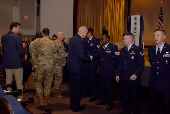 U.S. Air Force Col. Tony England, 17th Mission Support Group commander, shakes hands with graduates of the Community College of the Air Force during the Commencement Ceremony held at the theater on Goodfellow Air Force Base, June 21, 2019. The CCAF is a federally-chartered academic institution that serves the Air Force's enlisted total force. (U.S. Air Force photo by Senior Airman Seraiah Wolf/Released)