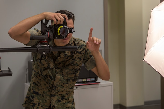 U.S. Marine Corps Lance Cpl. John Hall, a combat photographer assigned to Marine Corps Air Station (MCAS) Yuma, takes a picture in the promotion photo studio at MCAS Yuma, Ariz., June 17, 2019. As a combat photographer, Hall supports Marines aboard MCAS Yuma by taking promotion, re-enlistment, and command photos when needed. (U.S. Marine Corps photo by Sgt. Isaac D. Martinez)