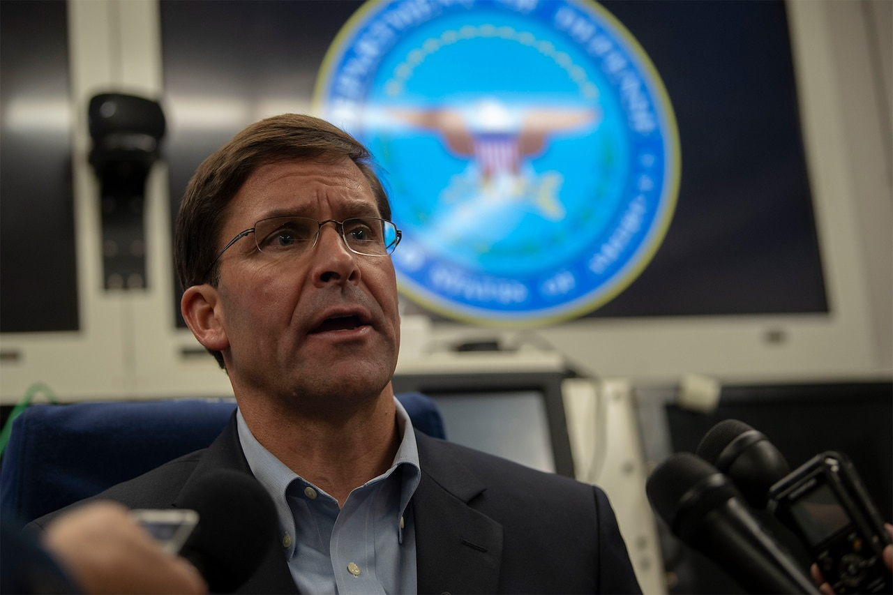 Acting Defense Secretary Mark T. Esper speaks with reporters on a government aircraft.