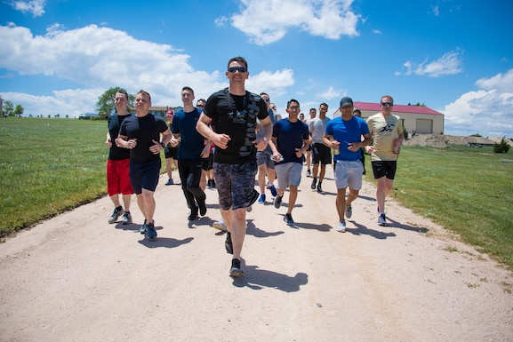 Airmen from the 50th Space Communications Squadron run in formation as part of the warmup during the obstacle course challenge at PCR Fitness, Colorado Springs, Colorado, June 21, 2019. The Airmen were divided into four teams to challenge each other while tackling multiple obstacles in the morale and team building event. (Air Force photo by 2nd Lt. Idalí Beltré Acevedo)