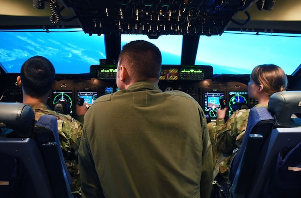 Participants of an Airman enrichment day pilot a C-5M Super Galaxy in the 60th Operations Group's state-of-the-art flying simulator June 14, 2019, at Travis Air Force Base, California. The Airman enrichment day was the first of its kind in the Air Force and exposed Airmen of different Travis units to the jobs and mission contributions of other Air Force jobs. (U.S. Air Force photo by Senior Airman Christian Conrad)