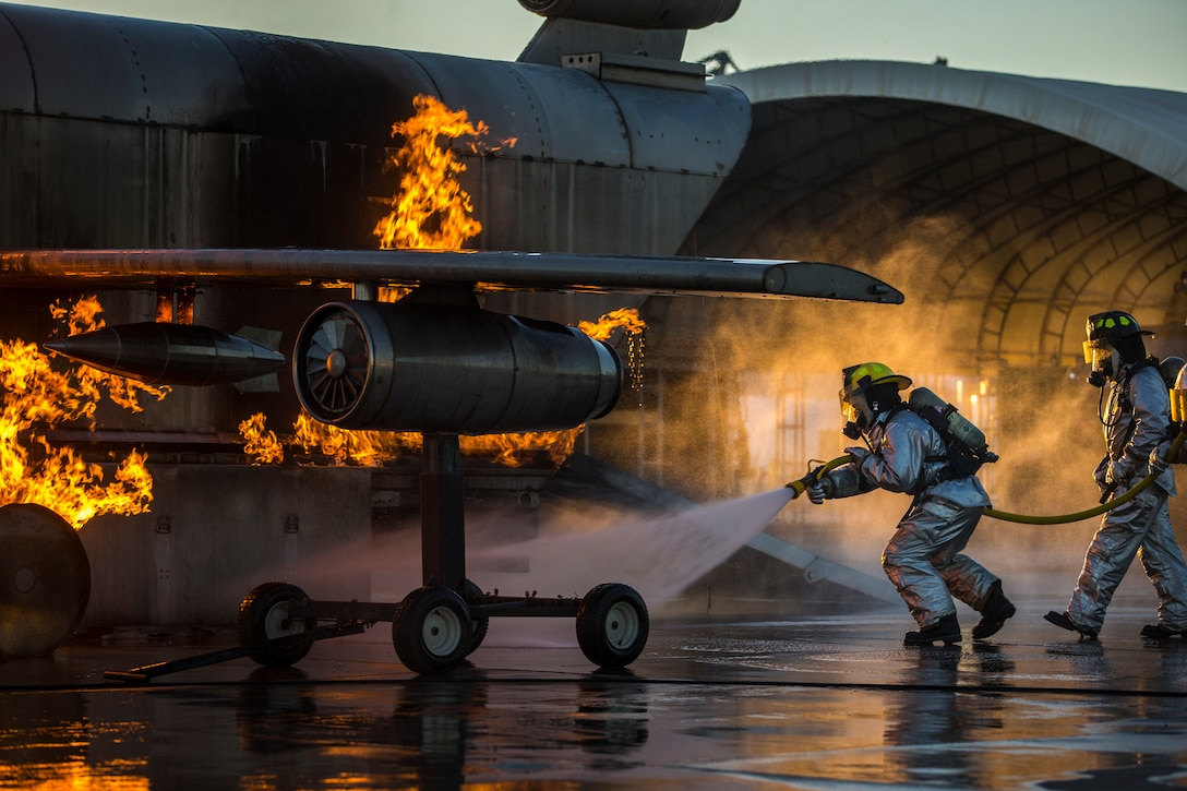 U.S. Marines with Aircraft Rescue and Firefighting, Headquarters and Headquarters Squadron (H&HS), Marine Corps Air Station Yuma conduct hand line drills during live burn training on MCAS Yuma, Arizona, June 25, 2019. Hand line drills focus on techniques to push fuel fires away from aircraft, ARFF Marines train monthly to enhance their readiness when responding to emergencies on the flight line.