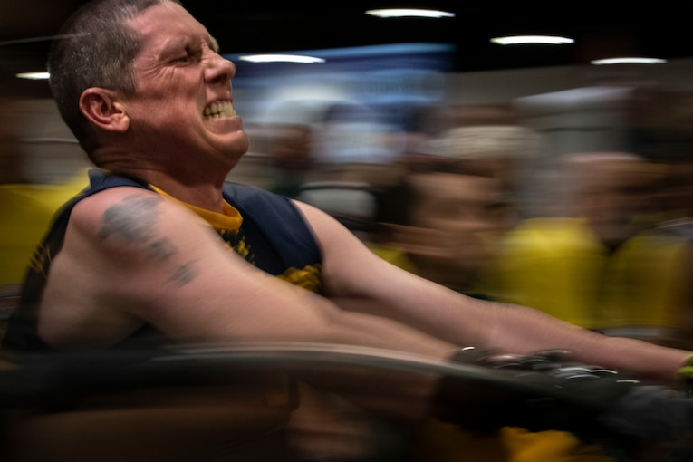 A military athlete grimaces as he takes part in a rowing competition.