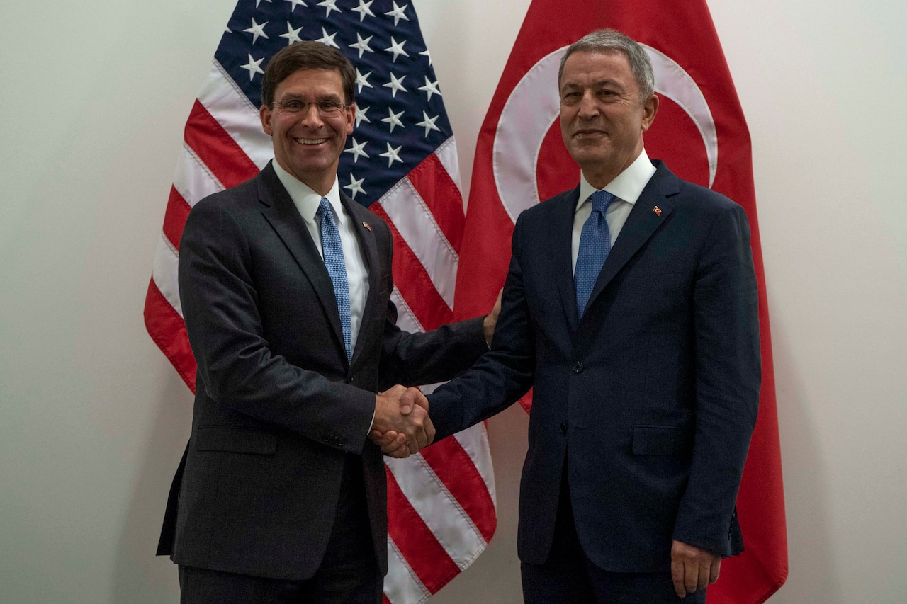 Acting Defense Secretary Mark T. Esper shakes hands with the Turkish defense minister in front of both nations' flags.