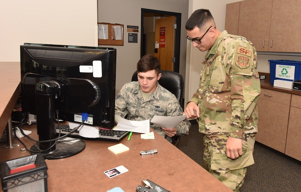 Senior Airman Wyatt Ovitt and Airman First Class Jonathan Mendoza, 50th SFS pass and identification badge clerks, inspect documentation to verify if an individual is authorized entry to the installation at the Visitor's Center, at Schriever Air Force Base, Colorado, June 25, 2019. Ovitt and Mendoza's flight make passes vetting personnel through a national law enforcement database to make sure the right people get on base in a timely manner. (U.S. Air Force photo by Staff Sgt. Matthew Coleman-Foster)