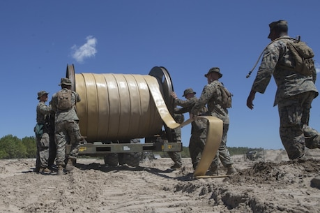 U.S. Marines with Bulk Fuel Company, 8th Engineer Support Battalion (ESB), 2nd Marine Logistics Group, utilize a hose-reel system to lay down a fuel line during a Bulk Fuel exercise at Camp Lejeune, North Carolina, June 19, 2019. The Marines with 8th ESB ran fuel lines, patrolled the fuel sites and provided all around security to remain proficient in fueling support operations. (U.S. Marine Corps photo by Lance Cpl. Adaezia L. Chavez)