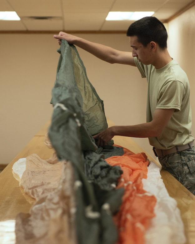 Airman Gareth Stubbs, 56th Operations Support Squadron Aircrew Flight Equipment apprentice, carefully inspects a parachute June 20, 2019, at Luke Air Force Base, Ariz.