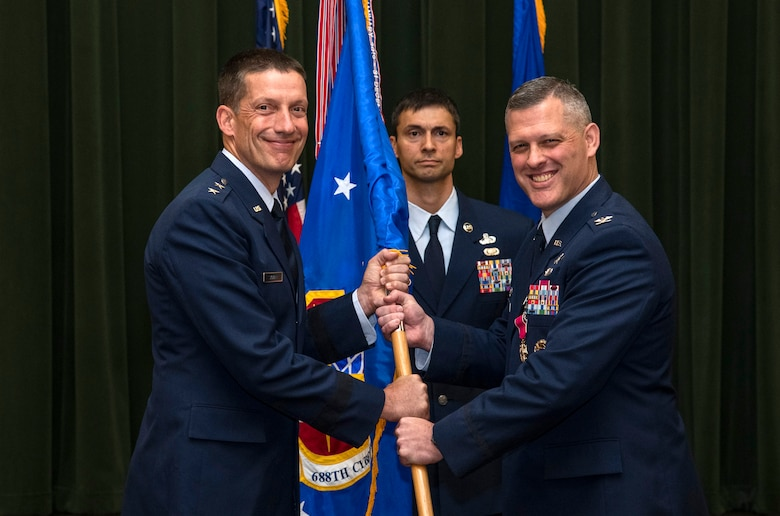 Col. Eric DeLange (right) relinquishes command of the 688th Cyberspace Wing to Maj. Gen. Robert Skinner, 24th Air Force commander, during the wing's change of command ceremony at Joint Base San Antonio-Lackland, Texas, June 25, 2019. Col. Steven Anderson took command of the 688th CW during the ceremony. (U.S. Air Force photo by Johnny Saldivar)