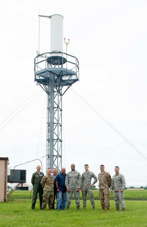 The Tactical Air Navigational System repair team pose for group photo in front of TACAN antenna June 22, 2019, at Offutt Air Force Base, Nebraska. They removed damaged components, replacing them and aligning the system and performing peak tuning to optimize electronics in preparation for the Federal Aviation Administration to certify newly installed system. (U.S. photo by L. Cunningham)