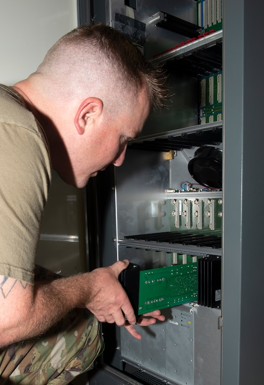 Master Sgt. Travis Meyer, 55th Operational Support Squadron Radar Airfield Weather Systems section chief, installs a circuit board into a Tactical Air Navigation System transponder cabinet June 22, 2019, at Offutt Air Force Base, Nebraska. The TACAN system was only two years old when the transponder cabinet in which it is housed was damaged by flood waters March 2019. While the outer shell remained intact, the inside components were ruined. (U.S. Air Force photo by L. Cunningham)