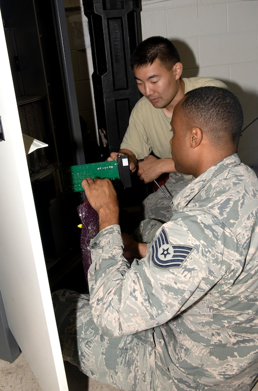 Tech. Sgt. Torrey Wilcox, right, 55th Operations Support Squadron Radar Airfield Weather Systems NCO in charge, and 1st Lt. Cody Park, center, 55th OSS, Airfield Operations Flight director of operations, dismantle and repackage damaged components from a Tactical Air Navigation System rack damaged by flood waters in March on June 22, 2019, at Offutt Air Force Base, Nebraska. The damaged components will be shipped back to the Thales Company to be refurbished. (U.S. photo by L. Cunningham)