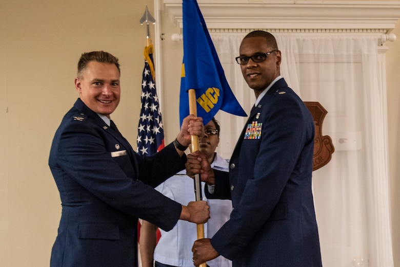U.S. Air Force Col. Christian Lyons, 20th Medical Group commander, left, hands the guidon to Lt. Col. Jamale Hart, incoming 20th Healthcare Operations Squadron commander, at Shaw Air Force Base, South Carolina, June 21, 2019.