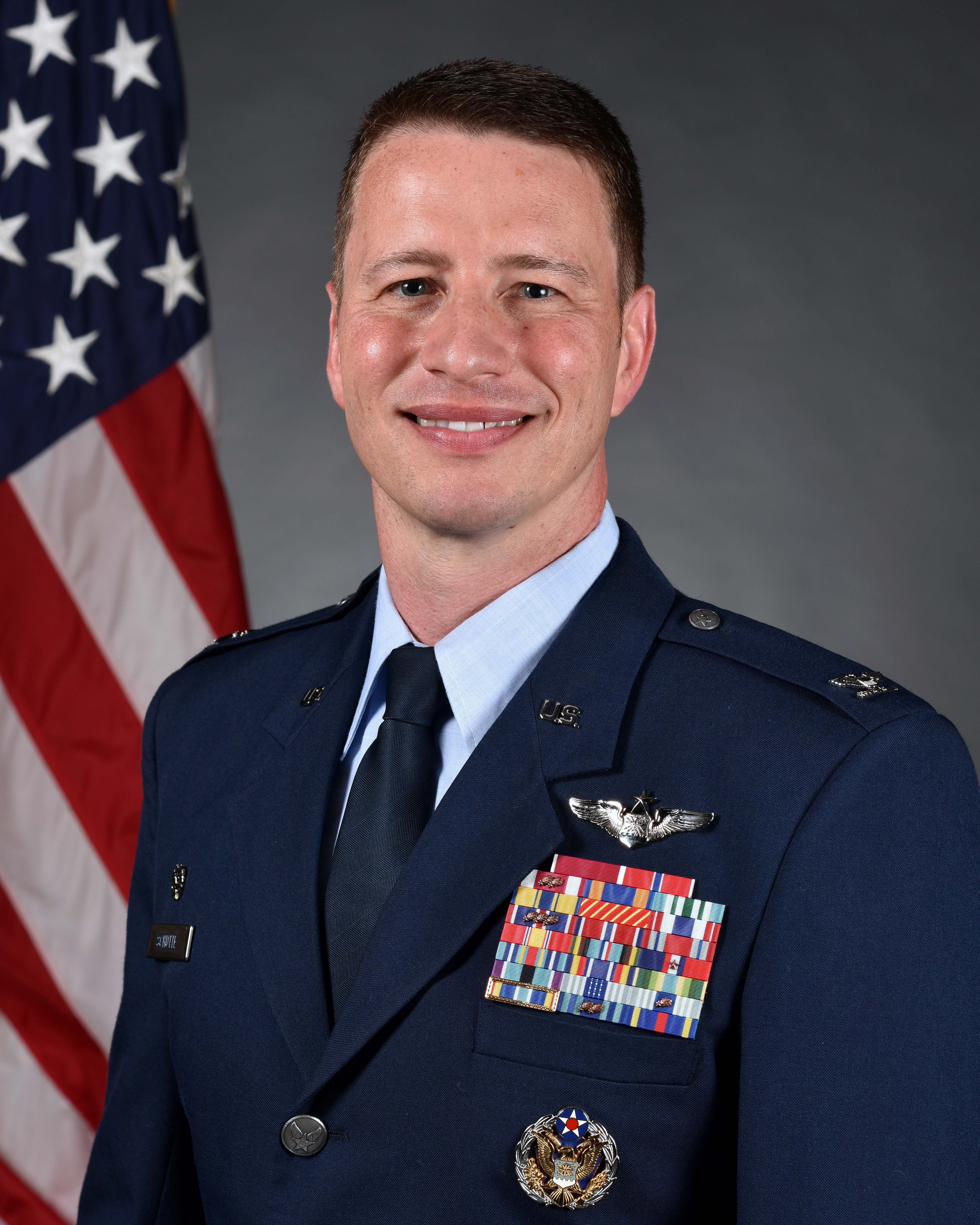 White man in Blue Air Force Uniform in front of Red, white and Blue American flag.