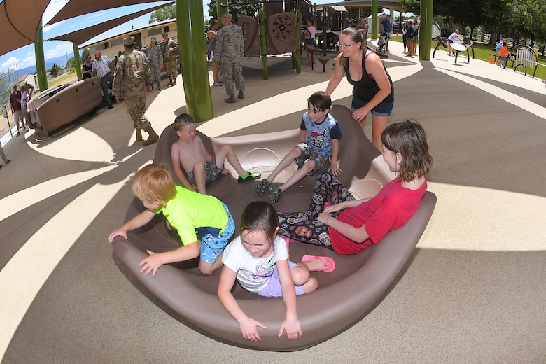 Rebecca McBride plays with children on the merry go-round at the new, all-abilities playground at Centennial Park June 24, 2019, at Hill Air Force Base, Utah. The playground is wheelchair accessible and incorporates sensory areas with a mixture of music- and texture-focused equipment for children. (U.S. Air Force photo by Todd Cromar)