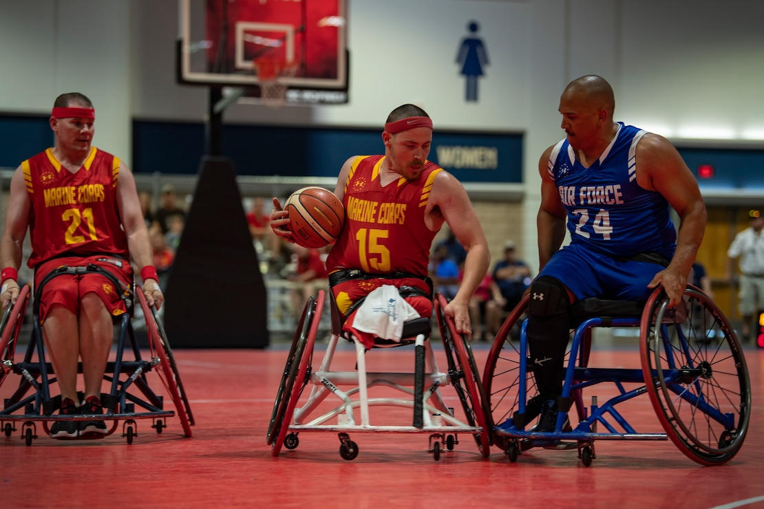 U.S. Marine Corps veteran Isaac Blunt fends off an Air Force defender at the DoD Warrior Games wheelchair basketball tournament in Tampa, Florida, June 24, 2019. The 2019 Warrior Games consist of 13 Paralympic-style sports, and more than 300 athletes representing the U.S. Marine Corps, Army, Navy, Air Force, Special Operations Command, and five international teams.
