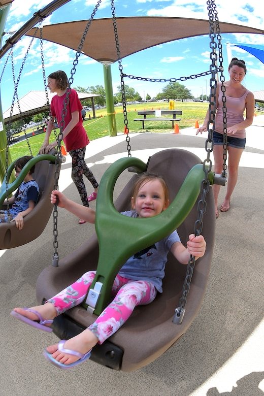 Skylar and her mother, Debbra Harvey, enjoy the new, all-abilities playground at Centennial Park June 24, 2019, at Hill Air Force Base, Utah. The playground is wheelchair accessible and incorporates sensory areas with a mixture of music- and texture-focused equipment for children. (U.S. Air Force photo by Todd Cromar)