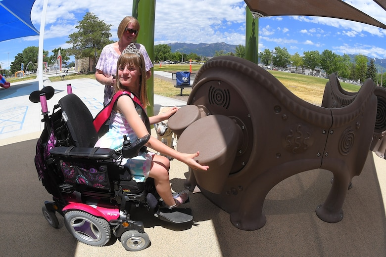 Brianna and her mother, Wendy Heim, enjoy the new, all-abilities playground at Centennial Park June 24, 2019, at Hill Air Force Base, Utah. The playground is wheelchair accessible and incorporates sensory areas with a mixture of music- and texture-focused equipment for children. (U.S. Air Force photo by Todd Cromar)
