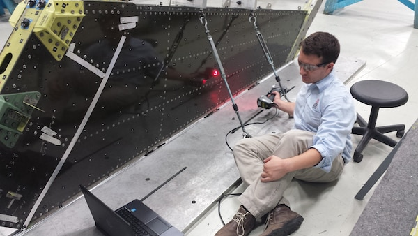 Solomon Duning, Research Engineer from The University of Dayton Research Institute, uses laser scanning technology to inspect an F-16 vertical tail on a depot fixture. (Courtesy photo)