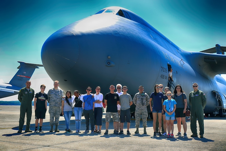 Members of the public, and Airmen, pose for a photo in front of a C-5M Super Galaxy during a tour, Westover Air Reserve Base, June 26, 2019. This event was the first of Westover's new monthly, public tours. (U.S. Air Force photo by Senior Airman Daniel Pedretti)
