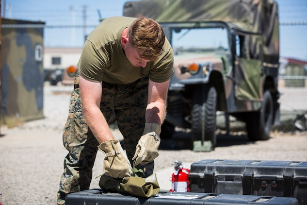 U.S. Marine Corps Motor Vehicle Operators assigned to Marine Unmanned Aerial Squadron (VMU) 1 gather issued gear together for placement in the 7-ton Medium Tactical Vehicle Replacement (MTVRs) and Humvee vehicles at Marine Corps Air Station Yuma, Ariz., June 18, 2019. The gear included basic vehicle repair items, tools, and first-aid items for the operators to use in case of emergency or mishap. (U.S. Marine Corps photo by Sgt. Isaac D. Martinez)