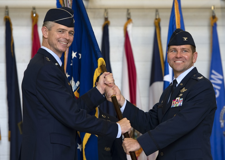 U.S. Air Force Col. Jon Wheeler, incoming 33rd Fighter Wing commander, takes the guidon from U.S. Maj. Gen. Craig Wills, 19th AF commander, during a change of command ceremony at Eglin Air Force Base, Florida, June 18, 2019.
