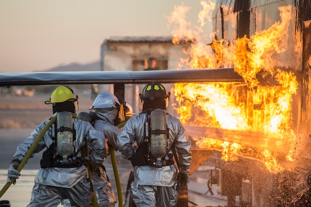 U.S. Marines with Aircraft Rescue and Firefighting (ARFF), Headquarters and Headquarters Squadron (H&HS), Marine Corps Air Station (MCAS) Yuma conduct hand line drills during live burn training on MCAS Yuma, Ariz., June 25, 2019. Hand line drills focus on techniques to push fuel fires away from aircraft, ARFF Marines train monthly to enhance their readiness when responding to emergencies on the flight line. (U.S. Marine Corps photo by Sgt. Allison Lotz)
