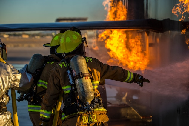 U.S. Marines with Aircraft Rescue and Firefighting (ARFF), Headquarters and Headquarters Squadron (H&HS), Marine Corps Air Station (MCAS) Yuma conduct hand line drills during live burn training on MCAS Yuma, Ariz., June 25, 2019. Hand line drills focus on techniques to push fuel fires away from aircraft, ARFF Marines train monthly to enhance their readiness when responding to emergencies on the flight line. (U.S. Marine Corps photo by Lance Cpl. John Hall)