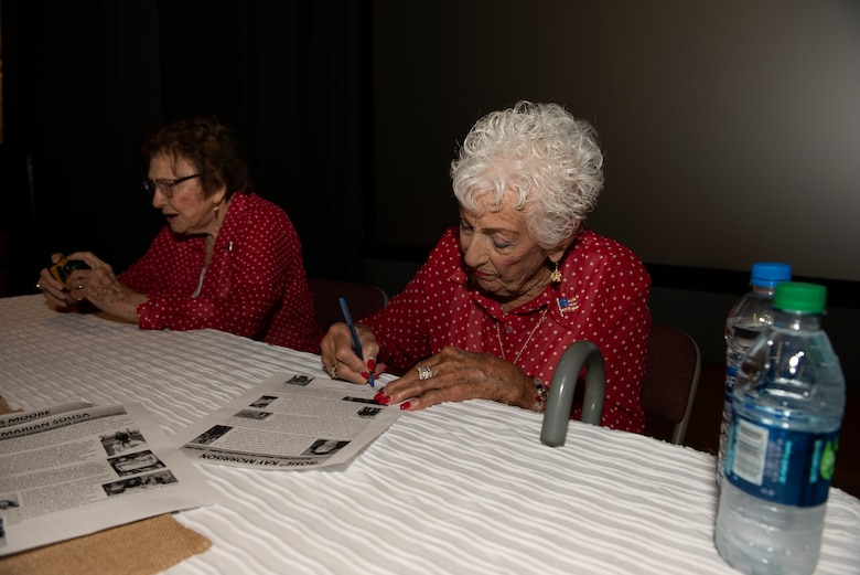 Kay Morrison, 95, signs a print out of her biography June 25, 2019, at Travis Air Force Base, California. Morrison is one of the many women known as 'Rosie the Riveter' as she worked as a welder in the Richmond, California, Kaiser Shipyard from 1943 – 1945. During a visit to Travis AFB, she and three other Rosies met with 60th Air Mobility Wing leadership, had lunch with Airmen and shared their experiences. (U.S. Air Force photo by Tech. Sgt. James Hodgman)