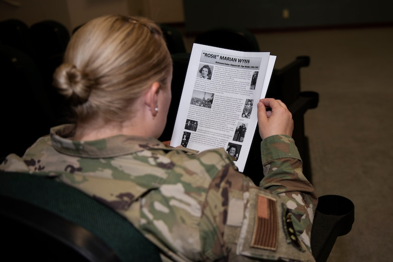 "U.S. Air Force Master Sgt. Shanna Peters, 60th Aerial Port Squadron traffic management cargo operations section chief, reads the biography of Marian Wynn, 92, prior to a 'Rosie the Riveter' presentation June 25, 2019, at Travis Air Force Base, California. Wynn is one of the many women known as ""Rosie"" as she worked as a pipe welder in the Richmond, California, Kaiser Shipyard from 1944 – 1945. During a visit to Travis AFB, she and three other Rosies met with 60th Air Mobility Wing leadership, had lunch with Airmen and shared their experiences. (U.S. Air Force photo by Tech. Sgt. James Hodgman)"
