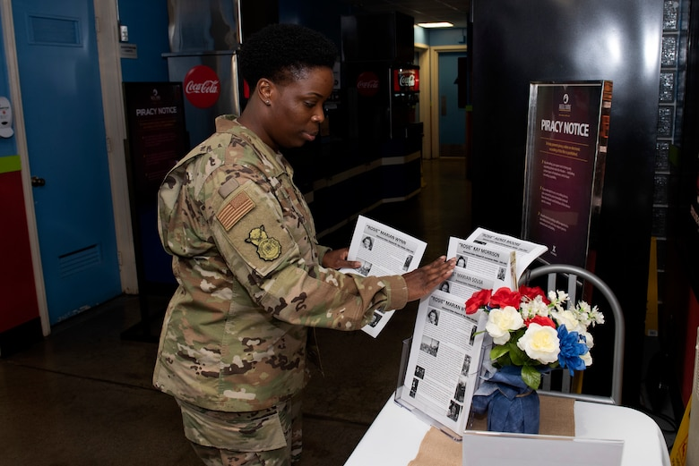 U.S. Air Force Tech. Sgt. Mernetta McCook, 60th Security Forces Squadron combat arms and armory operations flight chief, grabs the biographies of Agnes Moore, 99, Kay Morrison, 95, Marian Sousa, 93, and Marian Wynn, 92, before a 'Rosie the Riveter' presentation June 25, 2019, at Travis Air Force Base, California. During the presentation, the four women shared their experiences working at the Richmond, California, Kaiser Shipyard during World War II. (U.S. Air Force photo by Tech. Sgt. James Hodgman)
